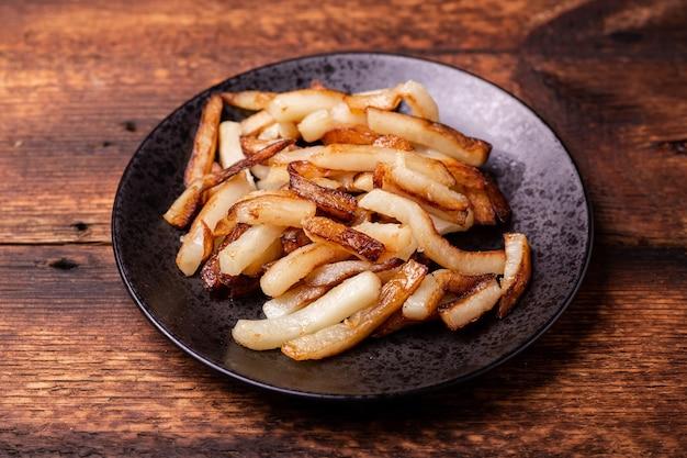 Жареный картофель на черной тарелке на деревянном фоне.