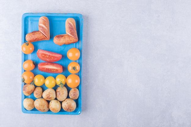 Patate fritte e salsicce sul piatto blu.