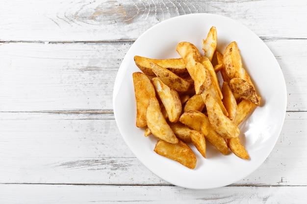 Жареный картофель ломтики чипсов на деревянный стол