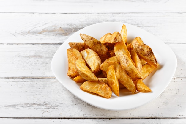 Fried potatoes slices chips on wooden table