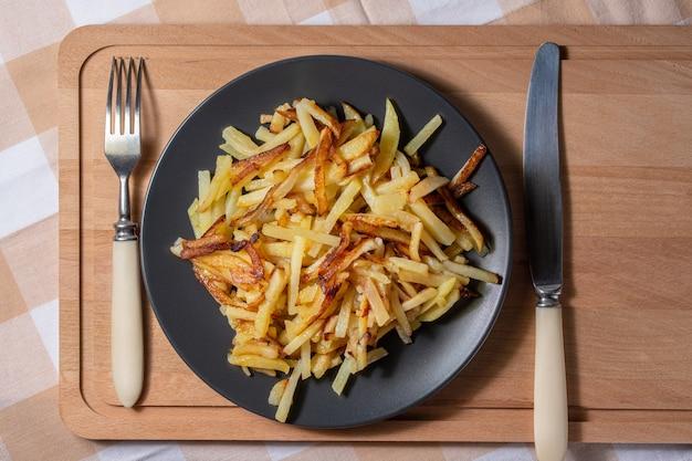 Жареный картофель с хрустящей корочкой на тарелке на фоне деревянной доски