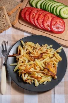Жареный картофель с хрустящей корочкой с хлебом и нарезанными овощами вид сверху