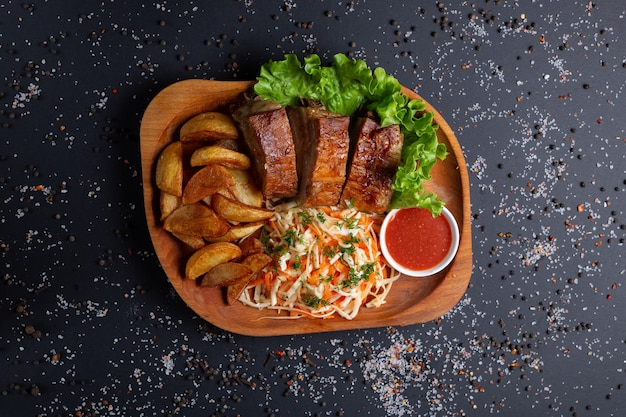 Fried potatoes with baked meat and salad, on black