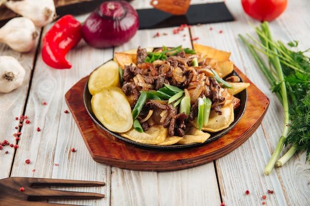 軽い木製のテーブルの上の鋳鉄鍋で牛肉とネギとフライドポテト