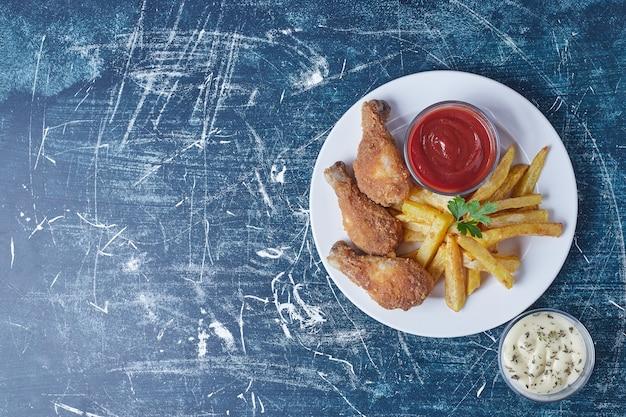Patate fritte con cosce di pollo e salse.