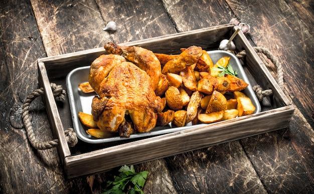 木製のテーブルのトレイに鶏肉とフライドポテト。