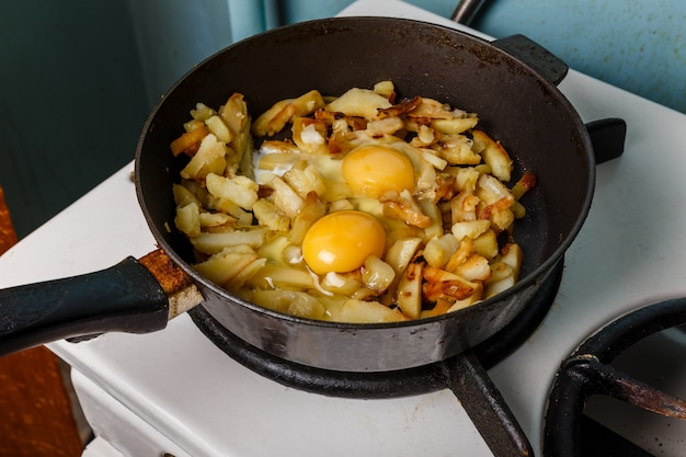 Fried potatoes with egg in a frying pan, food bachelor