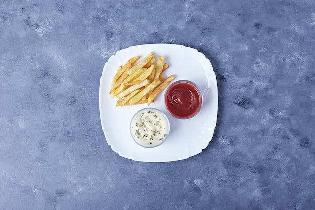 Patate fritte con erbe e salse.