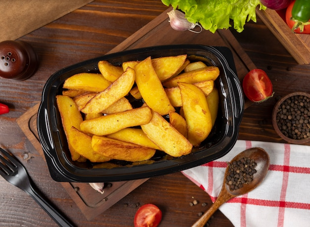 Fried potatoes with herbs takeaway in black container.