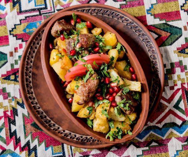 Жареный картофель с кусочками мяса в глиняном горшочке. европейская кухня