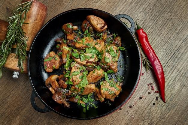 Жареный картофель со свининой, луком и зеленью в декоративной кастрюле на деревянной поверхности. вид сверху на вкусную еду.