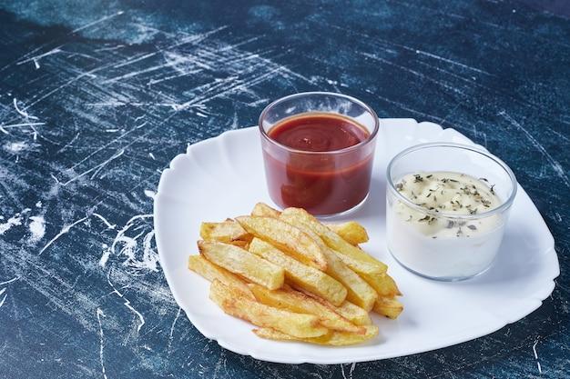 하얀 접시에 소스와 함께 튀긴 감자.