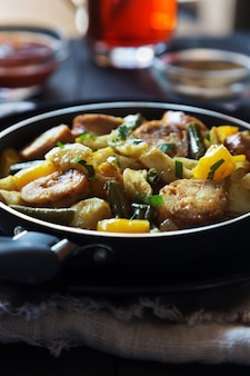 Fried potatoes with sausages, beans and pepper