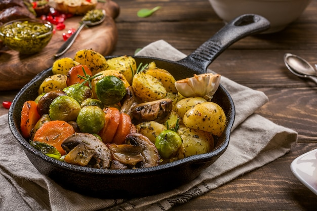 Fried potatoes with vegetables and herbs on wooden background. healthy food concept.