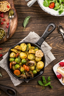 Fried potatoes with vegetables and herbs on wooden background.