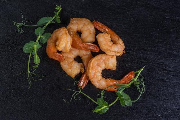 Жареные креветки на черном каменном подносе. морепродукты