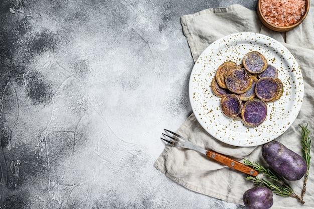 ピンクの塩で揚げた紫芋。灰色の背景。上面図。テキストのためのスペース