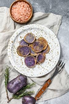 Жареный пурпурный картофель с розовой солью. серый фон вид сверху. пространство для текста