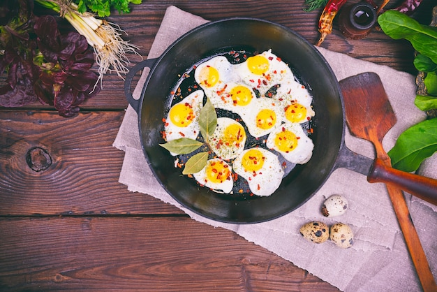 Fried quail eggs in a black cast-iron frying pan