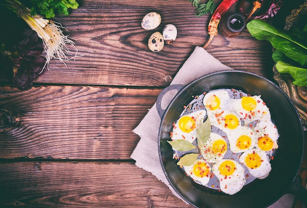 Fried quail eggs in a cast-iron frying pan