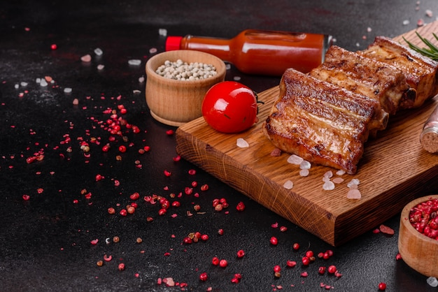 Fried ribs with rosemary, onion, sauce on a concrete background. dark table. place for text, copyspace