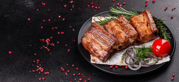 Fried ribs with rosemary, onion, sauce on a concrete surface. dark table. place for text, copyspace