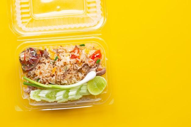黄色い表面のプラスチックの箱でチャーハン