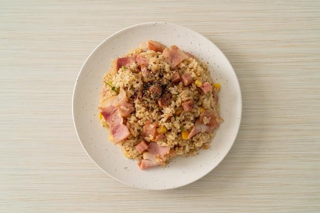 Жареный рис с ветчиной и черным перцем на белой тарелке