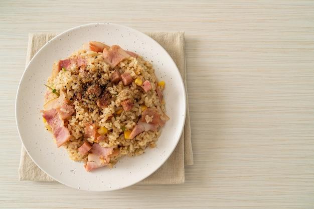 白い皿にベーコンハムと黒胡椒を添えたチャーハン