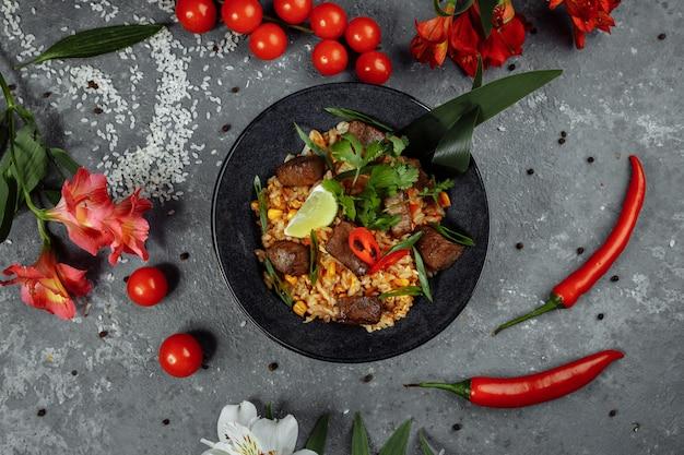 Жареный рис с говядиной и овощами на сером текстурированном фоне