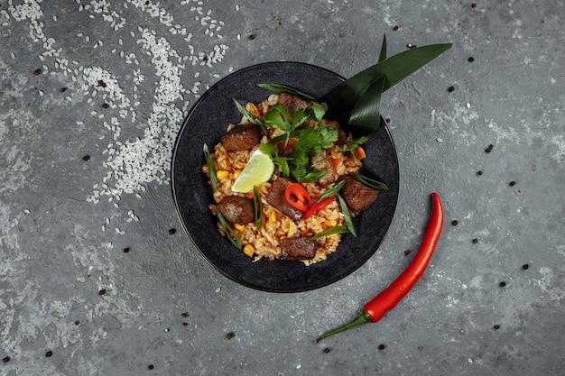 Жареный рис с говядиной и овощами на сером текстурированном столе.