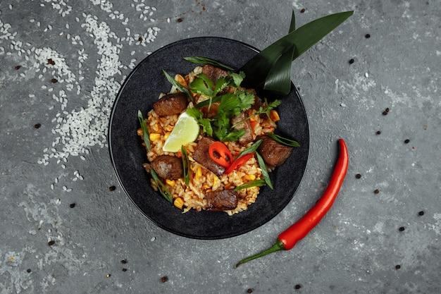 Жареный рис с говядиной и овощами на серой текстуре.