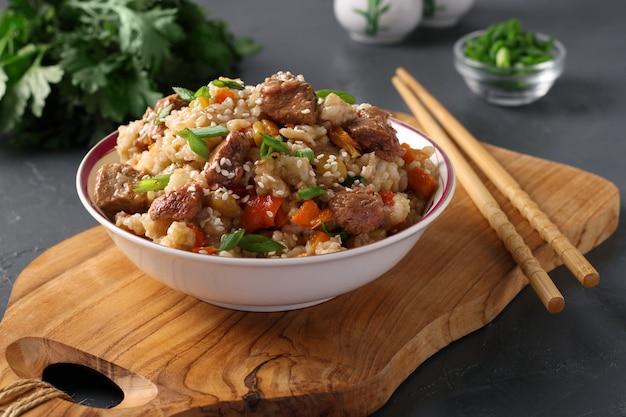 牛肉、野菜、にんにく、生姜、ねぎのチャーハンにゴマをまぶして、暗い背景の木板に。アジア料理。