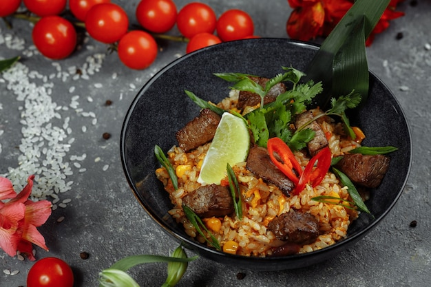 Fried rice with beef and vegetables on a gray table.
