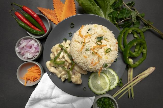 Жареный рис с курицей и овощами на темной тарелке и темном фоне
