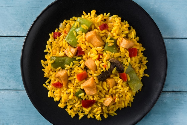 Fried rice with chicken and vegetables in black plate on blue wooden table close up