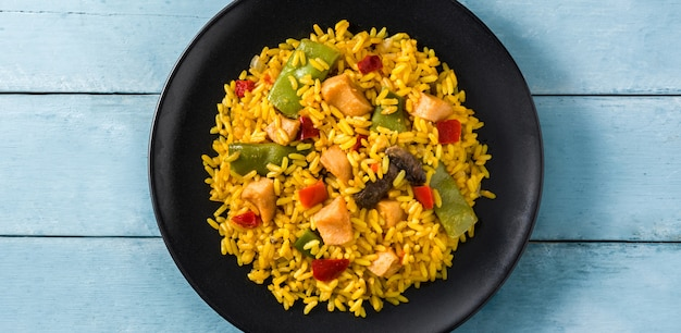 Fried rice with chicken and vegetables in black plate on blue wooden table panorama view