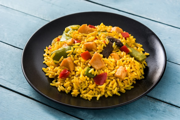 Fried rice with chicken and vegetables in black plate on blue wooden table.