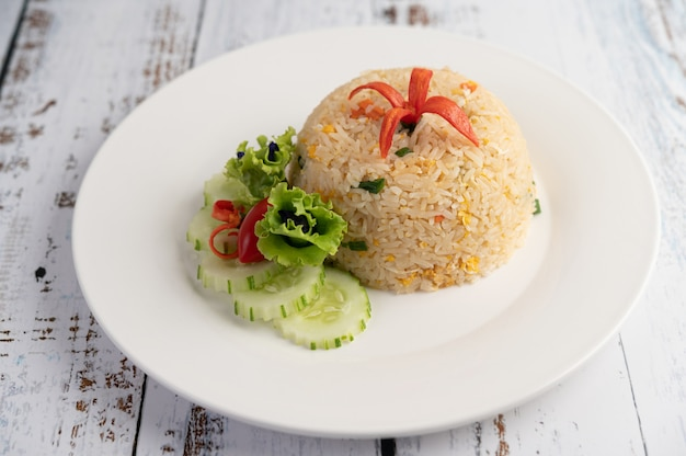 Fried rice with eggs in a white plate on wood surface