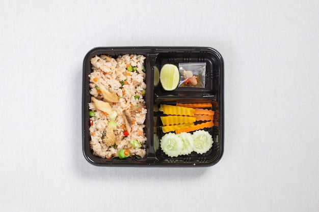 Fried rice with fried fish put in black plastic box, put on a white tablecloth, food box, thai food.