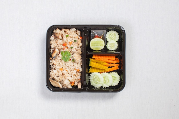 Fried rice with fried tuna put in black plastic box, put on a white tablecloth, food box, thai food.