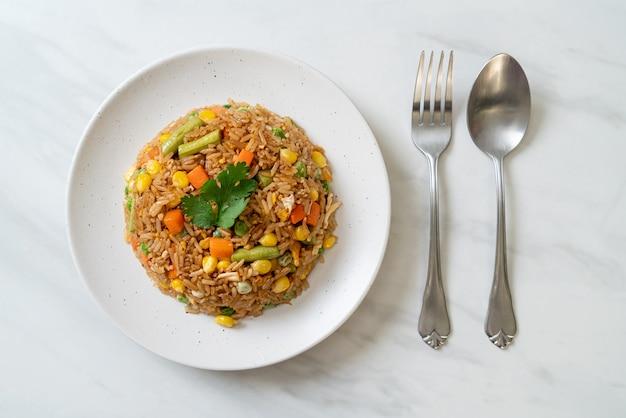 Жареный рис с зеленым горошком, морковью и кукурузой - вегетарианский и здоровый стиль питания Premium Фотографии