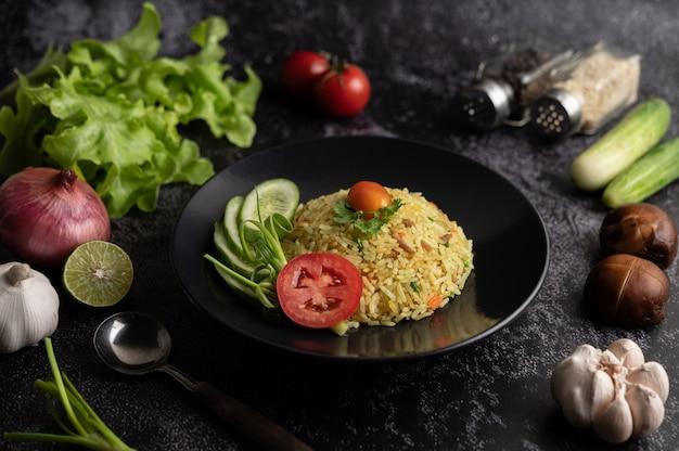 Жареный рис с фаршем из свинины, помидора, моркови и огурца на тарелке