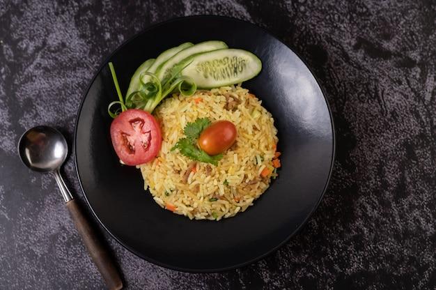 Riso fritto con carne di maiale macinata, pomodoro, carota e cetriolo sul piatto
