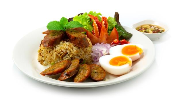 Жареный рис с тайской острой колбасой notrhern thai подается в стиле фьюжн отварное яйцо, острый рыбный соус и овощи, вид сбоку