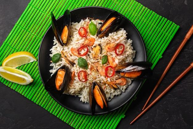 緑の竹マットと石のテーブルに箸を置いた黒いプレートにシーフードムール貝、エビ、バジルを添えたチャーハン。上面図。
