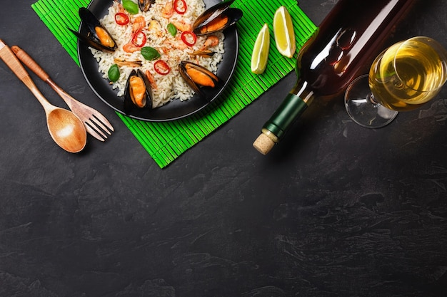 Fried rice with seafood mussels, shrimps, basil in a black plate with wineglass, lemon, wooden spoon and fork on green bamboo mat and stone table. top view.
