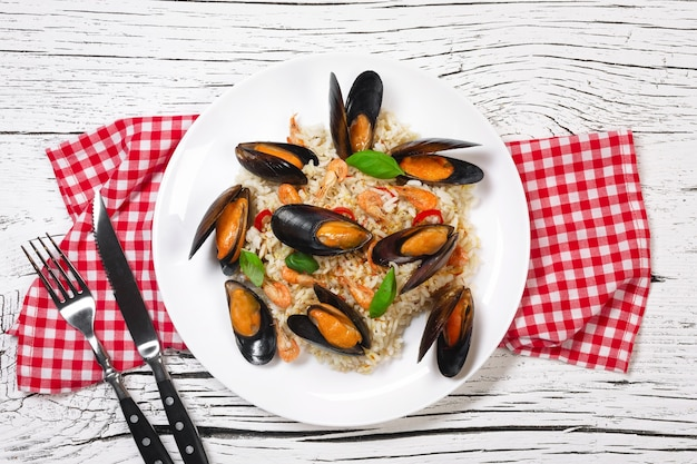 Fried rice with seafood mussels, shrimps and basil in a plate with towel, knife and fork on white cracked wooden table. top view.