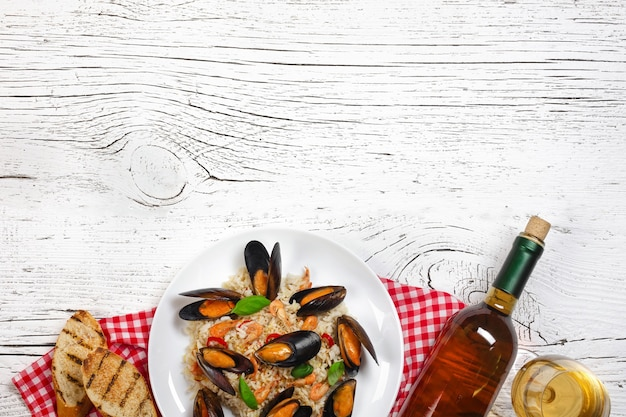 Fried rice with seafood mussels, shrimps and basil in a plate with wine bottle, wineglass, towel and toasted baguette on white cracked wooden table. top view.