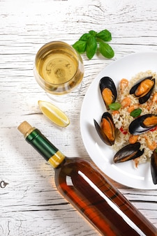 Fried rice with seafood mussels, shrimps and basil in a plate with wine bottle and wineglass on white cracked wooden table. top view.